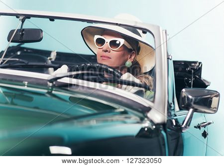 Woman in retro 1960s fashion with hat and shades driving convertible. poster