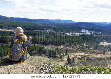 Woman sitting and looking at scenery over Elbow Valley in Kananaskis,Alberta,Canada.