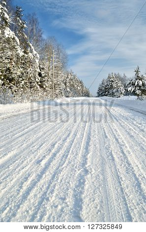 Snowcovered rural forest road through a forest in winter