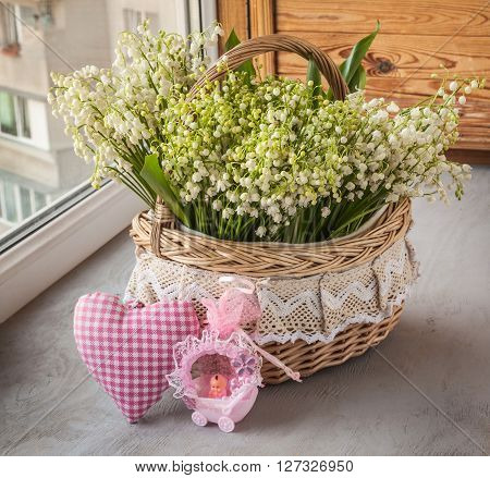 Basket with lilies of the valley (Convallaria majalis) next to heart and doll in the stroller (out production of mass production) on o the window