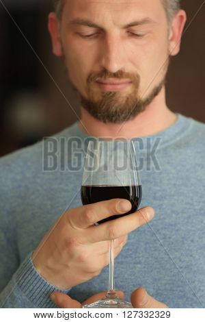 Handsome middle-aged man tasting red wine, close-up
