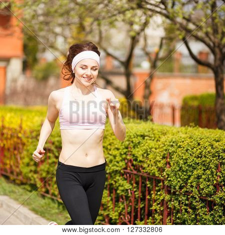 Young Happy Woman Jogging Along The Street