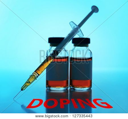 Stop doping concept. Medical ampule with syringe on blue background
