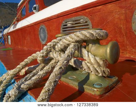 Ropes on a knot bollard against red boat