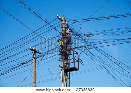 Two electric poles with many crossing cables
