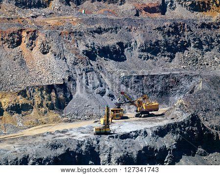 Excavator put metal ore to the dump-body track
