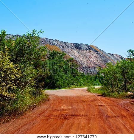 Red road near massive dump of depleted iron ore