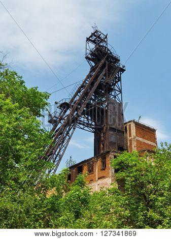 Abandoned iron ore mine headhear behind of green trees