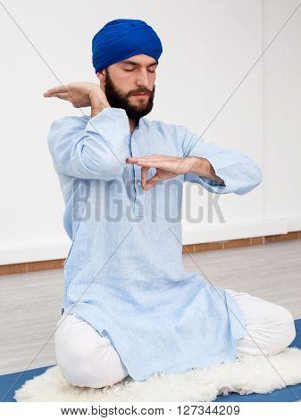 Man In A Turban Sitting On The Mat Doing Mudra