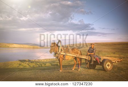 Horse Man Sitting On A Horse Cart In A Scenic View Of Nature Concept