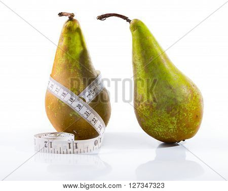 Two extended pears on a white background. In the middle of one of pears a centimetric tape