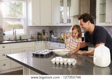 Caucasian girl and dad baking together in the kitchen