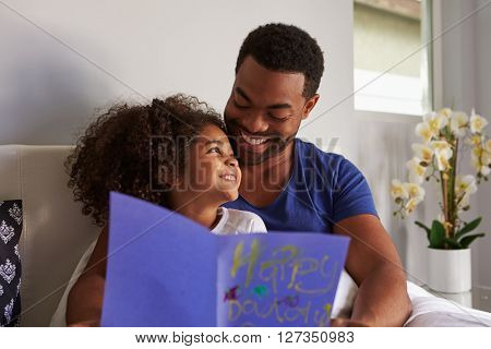 Happy dad and daughter in bed with card on birthday morning