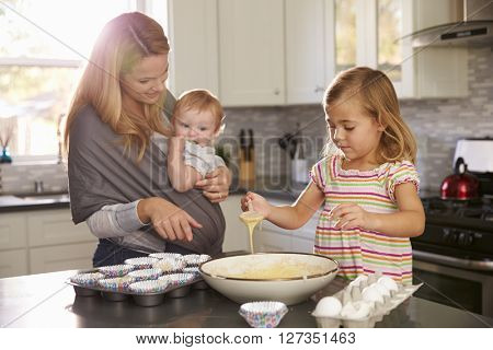 Young girl preparing cake mix in kitchen, mum showing baby