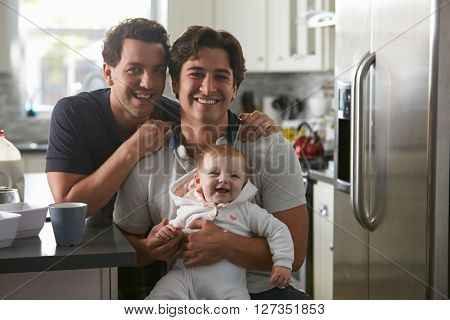 Male gay couple with baby girl in kitchen looking to camera