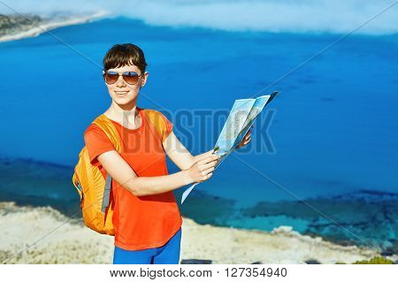 female traveler with backpack and map standing on the trail against sea and blue sky at early morning