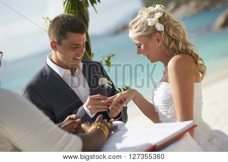 Couple Exchanging Rings During Wedding Registry Ceremony On Tropical Island.