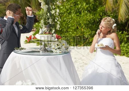 Lovely Couple Eating Wedding Cake During Tropical Marriage Ceremony.