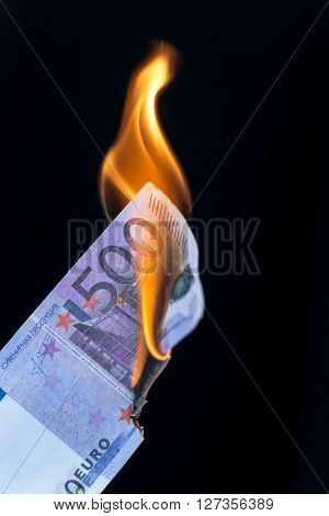 Single 500 EURO bankote on fire set against a black background with copy space area for finance waste themed ideas and concepts.