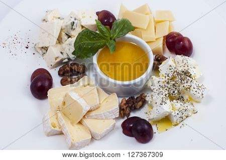 cuts of a variety of cheeses with grapes and nuts on a white plate