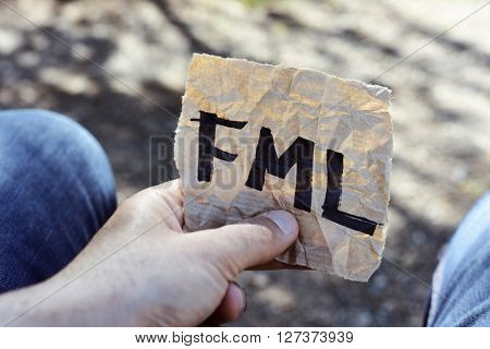 closeup of the hand of a young man holding a piece of paper with the text fml, for f... my life, written in it