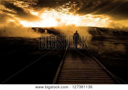 Man on walkway boardwalk with steam rising at sunset sunrise