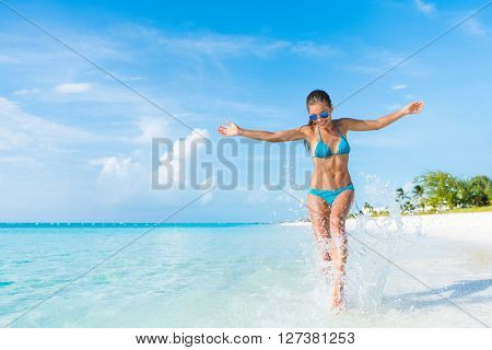 Freedom carefree girl playing splashing water having fun on tropical beach vacation getaway travel holiday destination. Playful woman with abs slim bikini body relaxing feeling free.