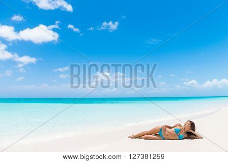 Sexy bikini suntan tan woman relaxing sun tanning on beach vacation luxury resort paradise getaway lying down on perfect white sand sunbathing in tropical Caribbean travel destination. Sky copyspace.