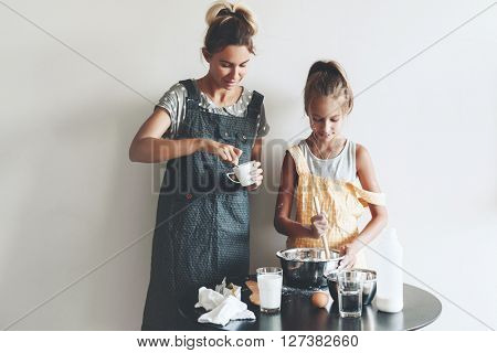 Mom with her 10 years old daughter dressed in linen aprons are cooking together over light wall, lifestyle photo series poster