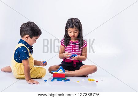indian small kids or asian brother and sister playing with colorful blocks over white background, cute little indian kids constructing house with blocks, indian kids playing with toys
