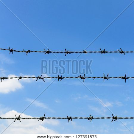 Barbed wire against blue sky and clouds