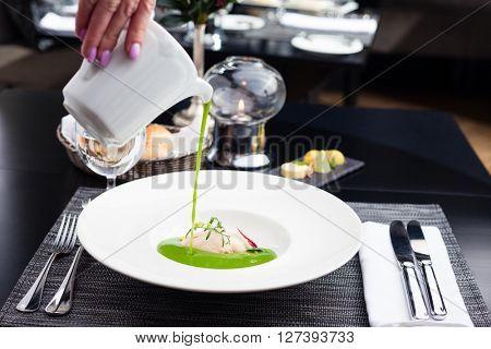 Broccoli cream soup with white fish and scallops