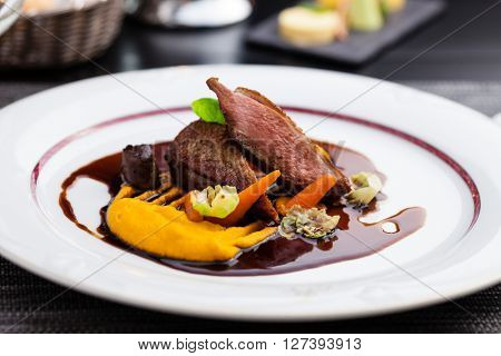 Roasted duck fillet with carrot-orange puree, slow-cooked duck heart and prune sauce