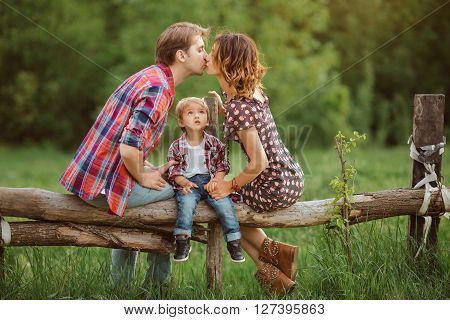 Happy Family on the nature. Mother father kissing and in casual clothes, sit on a fence, rural look , outdoors