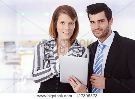 Attractive happy young caucasian businesswoman with tablet computer and handsome colleague at business office. Smiling, looking at camera, suit, copyspace.