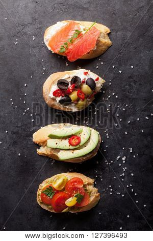 Toast sandwiches with avocado, tomatoes, salmon and olives on stone background. Top view