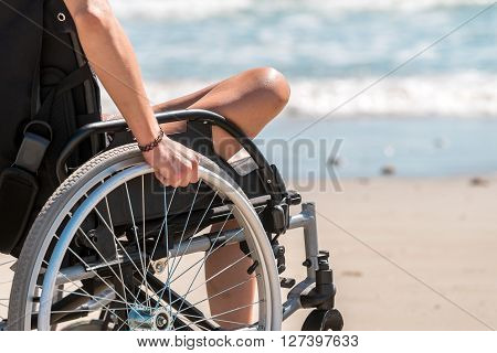 Disabled woman in the wheelchair at the beach