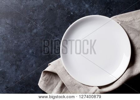 Empty plate and towel over stone table. Top view with copy space