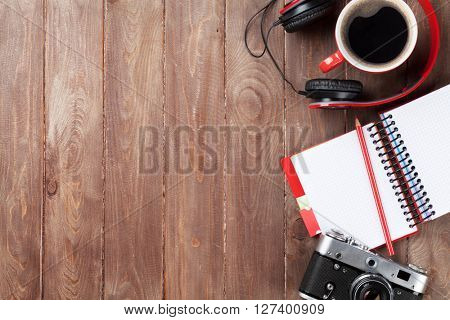 Set of travel stuff. Camera, headphones, notepad and coffee cup on wooden table. Top view with copy space