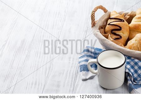 Fresh croissants basket and milk on wooden table. View with copy space