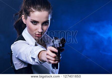 beautiful sexy girl holding gun . smoke background