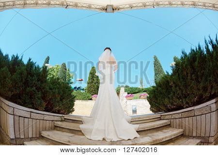 Back of bride with bridal bouquet standing on stairs in park ander modern roof. Fisheye lens photo