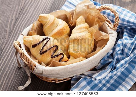 Fresh croissants basket on wooden table