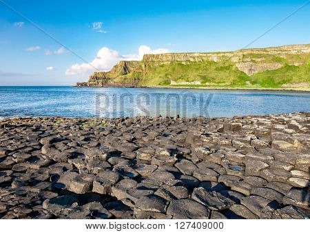 Giants Causeway unique geological hexagonal formations of volcanic basalt rocks and cliffs on Atlantic coast in County Antrim Northern Ireland in sunset light. UNESCO World Heritage site.