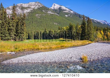 Magnificent valley in Banff National Park. Beneaped autumn stream with a pebbly bottom flows among the mountains and pine forests