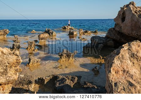 Quaint seascape Cavo Greco. Man stands on the border of chaos stone and looking at the sun
