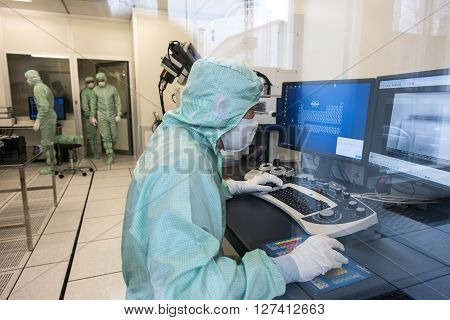 Saint-Petersburg Russia - April 18 2016: Engineer in microelectronics clean room behind the glass in the process. The company for the production of precision electronic circuits and devices.