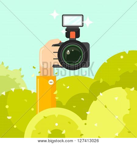 Paparazzi hand holds photo camera vector illustration. Spy hides in green bushes with photo camera. Journalists sit in ambush and make sensational shot. Paparazzi concept in flat style