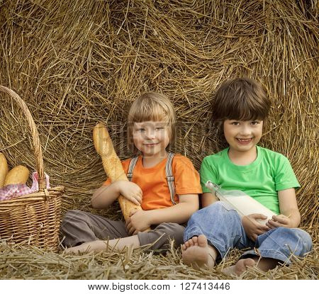two boy on a haystack with bread and milk