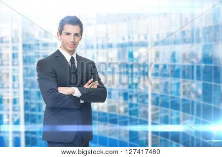 Portrait of business man with crossed hands, blue background. Concept of leadership and success